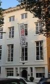foto van Koopmanshuis, met gebosseerde, natuurstenen lijstgevel. In de door een cordonlijst van de bel-etage gescheiden onderpui een rijk gesneden voordeur, Lodewijk XIV. Rijke interieurs in Lodewijk XIV, XV- en XVI-stijl