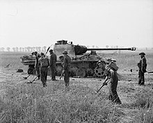 Royal Engineers sweep for mines around a destroyed German tank