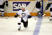 Photo de Ryan Whitney un genou sur la glace.