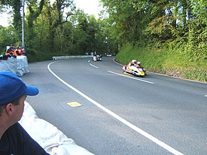 Sarah's Cottage, Isle of Man - View from Sarah's Cottage uphill towards the Creg Willey's area, with sidecars returning to Paddock in wrong direction after a Red Flag race stoppage caused by a competitor crash during 2009