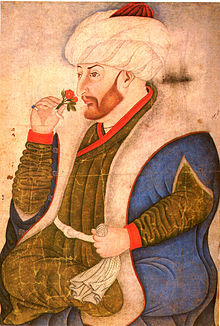 A corpulent bearded young man holding a rose and wearing a turban