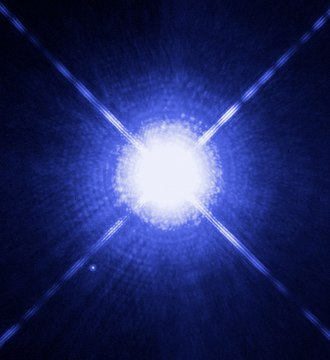 White - Image of Sirius A and Sirius B taken by the Hubble Space Telescope. Sirius B, a white dwarf, is the faint pinprick of light to the lower left of the much brighter Sirius A.