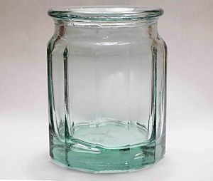 Glass - A jar made of soda-lime glass. Although transparent in thin sections, the glass is greenish-blue in thick sections from impurities. Bubbles remained trapped in the glass as it cooled from a liquid, through the glass transition, becoming a non-crystalline solid.