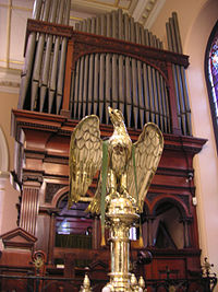 The brass lectern is in the traditional form of an eagle and the organ pipes are shown behind it.
