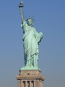 Statuego de vestita virinfiguro kiu portas torĉon en ŝi levis maldekstran manon kaj tablojdon en ŝia alia mano