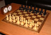 Pieces at the start of a game and a chess clock.