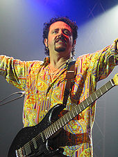 A man in a multi-colored dress shirt with a black guitar strapped around his neck.