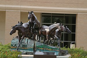 George Bush Presidential Library - A statue of horses leaping over pieces from the Berlin Wall stands on the plaza of the library. The statue depicts the fall of the wall in 1989, when Bush was president.