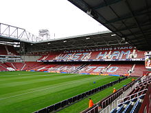 "A stand from a football stadium with laid out turf and two adjacent goals in the foreground. On the claret stands are the words written in sky blue capitals ""Sir Trevor Brooking stand"" on top of the larger words ""West Ham United"". There are men in orange jackets scattered around the stadium."