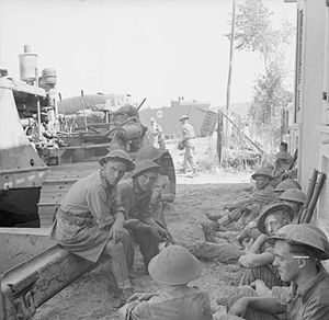 231st Brigade (United Kingdom) - Troops of the 231st Brigade resting beside a bulldozer after fighting a fire on a landing craft which was hit during a surprise landing in the enemy's rear at Porro Di S. Venere, Italy, 8 September 1943.