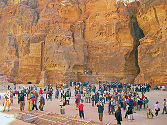 Tourism in Jordan - Tourists photograph Al Khazneh (not visible) upon arriving in Petra. The Siq can be seen on the right.