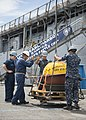 U.S. Sailors assigned to the amphibious dock landing ship USS Pearl Harbor (LSD 52) load a Pacific Islands Ocean Observing System wave buoy onto the flight deck of the ship in Pearl Harbor, Hawaii, during 130521-N-SP369-080.jpg