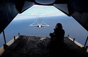 Air-to-air photography - A U.S. Navy Photographers Mate photographing an F/A-18 Hornet from the cargo ramp of a C-2 Greyhound.