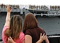 US Navy 050716-N-0050T-104 Two women wave goodbye to the Sailors and Marines manning the rails of the amphibious transport dock USS Cleveland (LPD 7) before departing Naval Station San Diego.jpg