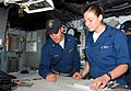US Navy 070418-N-9689V-006 Ensign Brandon Doll, reviews the ship's position with Quartermaster Seaman Apprentice Angela Stewart.jpg