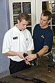 "US Navy 071212-N-3398B-012 Lt. Cmdr. Ed Rohrbach explains how to clear the chamber of a Sig Sauaer P-226 to Brad Keselowski, the driver of NASCAR's No. 88 Navy ""Accelerate Your Life"" Chevrolet car.jpg"