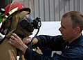 US Navy 090508-N-5292M-147 Damage Controlman 2nd Class Adam Duford assists HT3 Lee Bassett in donning his gear during the firefighting ensembles (FFE) race during the Damage Control Marathon at the Farrier Fire Fighting compoun.jpg