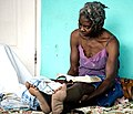 US Navy 100119-N-6266K-090 An elderly Haitian woman reads the Bible while waiting for medical treatment at Gheskio Field Hospital in Haiti.jpg