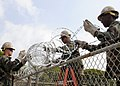 US Navy 100816-N-6357K-001 Seabees assigned to the camp maintenance department of Naval Mobile Construction Battalion (NMCB) 7 install protective razor wire at the Camp Mitchell weapons armory at Naval Station Rota, Spain.jpg