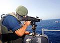 US Navy 110510-N-BZ392-531 Gunner's Mate 3rd Class Justin Pruett fires an M-240 machine gun at a floating target during a gun exercise aboard the g.jpg