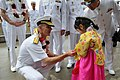 US Navy 110929-N-WW409-125 Rear Adm. J.R. Haley, commander of Task Force 70, presents a coin to a girl during a welcoming ceremony for the arrival.jpg