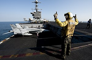 US Navy 111229-N-OY799-238 Aviation Boatswain's Mate (Handling) 2nd Class Roberto Andiarena signals for the raising of aircraft elevator one on the.jpg