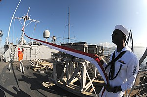 US Navy 120123-N-BK435-034 Boatswain's Mate Seaman Devon Nelson, assigned to the submarine tender USS Frank Cable (AS 40), holds up the 165-foot Ho.jpg