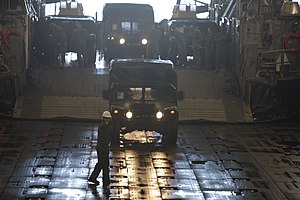 US Navy 120131-M-DK975-007 Marines assigned to Combat Cargo, embarked aboard the amphibious assault ship USS Kearsarge (LHD 3), unload humvees from.jpg