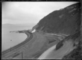 View of a train rounding Rocky Point in 1908 after the track was moved nearer the harbour following partial reclamation, between Wellington and Petone. ATLIB 277762.png