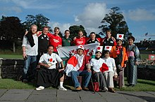 group of thirteen supporters pose together, some wearing rugby