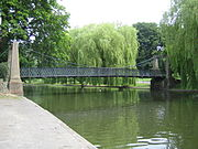 A pedestrian suspension bridge spans the boating lake in Wardown Park.