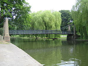 River Lea - A pedestrian suspension bridge spans the boating lake created where the widened river flows through Wardown Park in Luton.