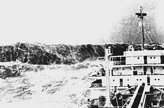 Rogue wave - Merchant ship labouring in heavy seas as a huge wave looms ahead, ca. 1940. Huge waves are common near the 100-fathom line in the Bay of Biscay.