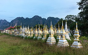 White and golden graves in a Buddhist cemetery at sunrise in Vang Vieng, Laos.jpg