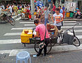 Woman preparing food from bike on street in Shanghai.jpg