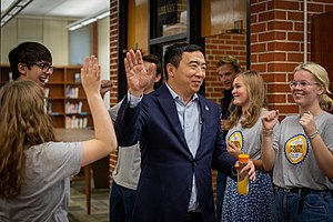 Yang is in the middle of giving a volunteer a high-five.