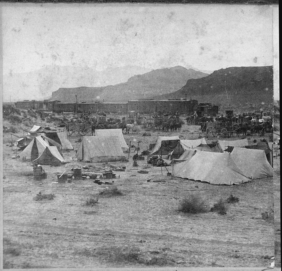 """End of the Track. Near Humboldt River Canyon, Nevada."" Campsite and train of the Central Pacific Railroad at foot of mo - NARA - 533792"