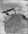 """""""The 175-foot boom of the conveyor stacker section discharging material from the east side, 7,000 feet distant."""" - NARA - 294005.tif"""