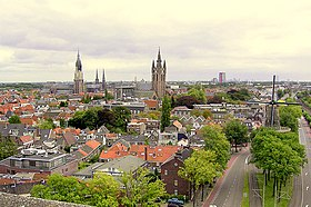 Aerial view of Delft with, from left to right, three churches, a university tower building and a windmill