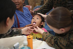 Marine Wing Support Squadron 172 - Ziraphinya Somari, center, sticks her tongue out for multinational medical professionals during a cooperative health engagement in Sukhothai, Thailand, February 13, 2014, during exercise Cobra Gold 2014.