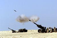 A 155mm M198 howitzer firing a shell.