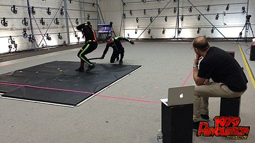 Two actors perform in dark suits on a motion capture stage, surrounded by cameras. The director looks on from the side.