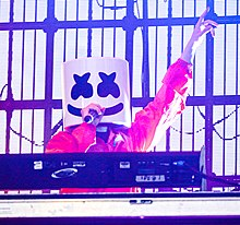 Marshmello holding a microphone in his right hand with his left hand raised up