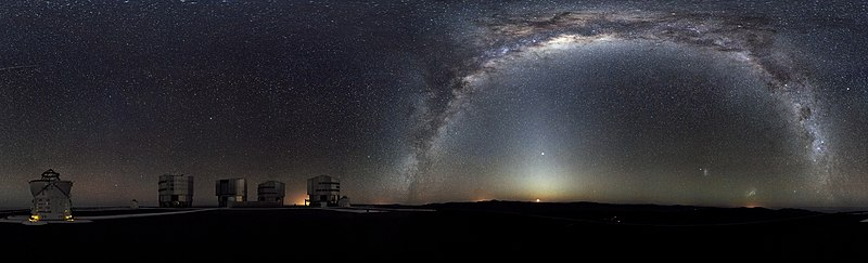 The Milky Way arches across this 360-degree panorama of the night sky above the Paranal Observatory, home of ESO's Very Large Telescope. The Moon is just rising and the zodiacal light shines above it, while the Milky Way stretches across the sky opposite the observatory. To the right in the image and below the arc of the Milky Way, two of our galactic neighbours, the Small and Large Magellanic Clouds, can be seen. The open telescope domes of the world's most advanced ground-based astronomical observatory are all visible in the image: the four smaller 1.8-metre Auxiliary Telescopes that can be used together in the interferometric mode, and the four giant 8.2-metre Unit Telescopes. The image was made from 37 individual frames with a total exposure time of about 30 minutes, taken in the early morning hours.