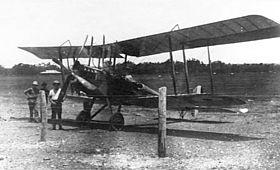 Biplane on landing ground with two men beside it