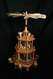 Christmas pyramid German Christmas decoration comprising a pyramidal frame with candle holders and a central carousel with a rotor at the top driven by candles' warm air, decorated with nativity scenes, angels, wise men, miners, forest scenes, etc.