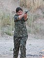 A YPJ fighter prepares to fire her handgun.jpg