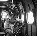 A crewman on board an RAF Coastal Command Lockheed Hudson of No. 269 Squadron, using an F.24 camera during an ice patrol from Kaldadarnes in Iceland, 5 May 1942. CS177.jpg