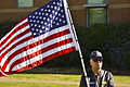 A member of the Patriot Guard Riders holding an American flag.jpg