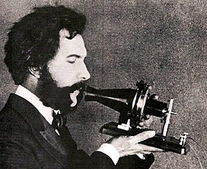History of the telephone - Actor portraying Alexander Graham Bell in a 1926 silent film. Shows Bell's first telephone transmitter (microphone), invented 1876 and first displayed at the Centennial Exposition, Philadelphia.